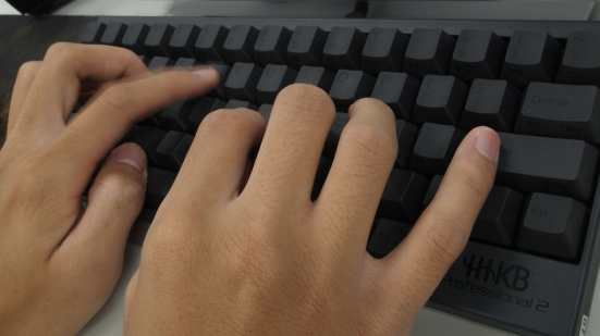 Typing with all ten fingers on a black keyboard